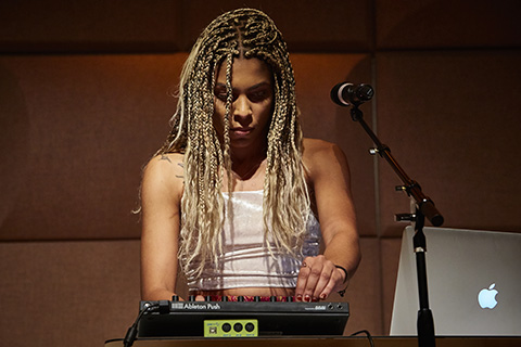Woman on stage playing a drum machine
